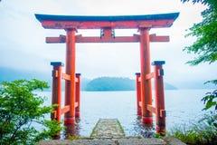 明亮的红色Torii门在Ashi湖中,与山的破火山口水域淹没了在背景 箱根寺庙,宁可神奈川 免版税图库摄影