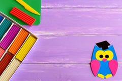 明亮的纸猫头鹰、五颜六色的彩色塑泥集合、塑料委员会和刀子在木背景与空白文本的 免版税库存图片