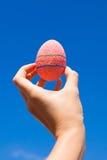 明亮的美丽的桃红色复活节彩蛋在手中  免版税库存照片