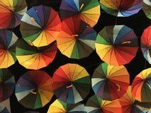 明亮的色的伞,绘在调色板的所有原色,以黑暗的夜空为背景 免版税库存照片
