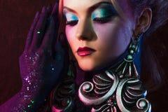 明亮的艺术构成的年轻可爱的白肤金发的女孩,在紫色口气 假钻石和闪烁身体绘画 免版税库存图片