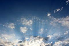 明亮的蓝天的概念性图象与放出通过松的云彩的阳光的 免版税库存图片