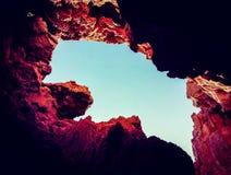 明亮的蓝天的看法通过在岩石的一个空白 免版税库存照片