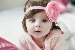 明亮的蓝眼睛的beauity 6个仔细地月大女婴看在照相机 免版税库存图片