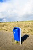 明亮的蓝色在一个空的海滩的回收站 免版税库存照片