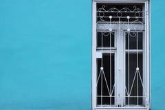 明亮的蓝色墙壁和白色老窗口与酒吧 简单派 库存照片