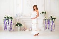 明亮的衣物的美丽的孕妇在内部 免版税库存图片
