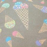 明亮的衣裳的一个小男孩画与白垩的冰淇凌在 免版税图库摄影