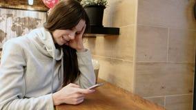明亮的衬衣的微笑的年轻深色的妇女按摩在她手机和微笑的坐的在咖啡馆 股票视频