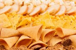 明亮的辣黄色快餐收藏-玉米花,烤干酪辣味玉米片,土豆片,油煎方型小面包片,玉米黏附作为背景 免版税库存照片