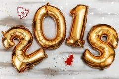 明亮的金属金子迅速增加图2018年,圣诞节,有闪烁星的新年气球在白色木桌上 免版税库存图片