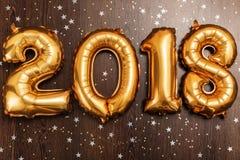 明亮的金属金子迅速增加图2018年,圣诞节,有闪烁星的新年气球在黑暗的木桌背景 免版税库存图片