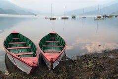 明亮的颜色两条小船:白色亚麻布和绿色和红色里面,停放在湖的岸,在背景中许多其他小船, 免版税库存照片