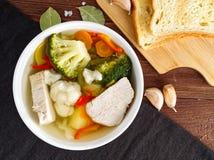 明亮的饮食汤用火鸡肉、花椰菜、硬花甘蓝和其他菜在棕色木背景,顶视图 库存照片