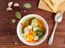 明亮的饮食素食汤用花椰菜、硬花甘蓝和其他菜在棕色木背景,顶视图 图库摄影