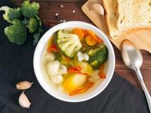明亮的饮食素食汤用花椰菜、硬花甘蓝和其他菜在棕色木背景,顶视图 库存图片