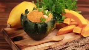 明亮的鲜美被制成菜泥的南瓜汤在与成份的一个被挖空的南瓜服务 股票视频