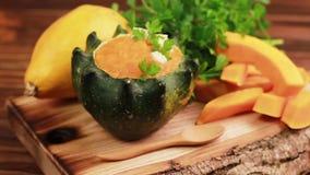 明亮的鲜美被制成菜泥的南瓜汤在与成份的一个被挖空的南瓜服务 股票录像