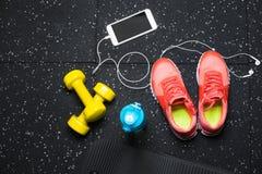 明亮的黄色哑铃、席子、瓶水,体育鞋子和电话顶视图在黑地板背景 免版税库存照片