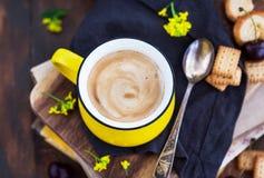 明亮的黄色杯子新鲜的热的无奶咖啡和甜点在夏天背景 免版税库存照片