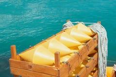 明亮的黄色标志浮体和绳索在一个木箱有蓝色t的 库存照片