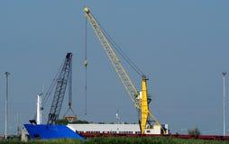 明亮的黄色码头起重机在工作在港口船坞:在附近有一台黑起重机 库存图片