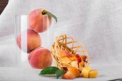 明亮的水多的桃子的构成在灰色织品背景的 三个整个桃子特写镜头在一个玻璃花瓶的 库存图片
