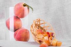 明亮的水多的桃子的构成在灰色织品背景的 三个整个桃子特写镜头在一个玻璃花瓶的 库存照片