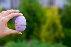 明亮的紫色复活节彩蛋在手中在背景  库存照片