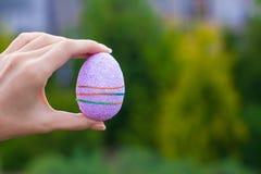 明亮的紫色复活节彩蛋在手中在背景  免版税图库摄影