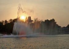 明亮的黄色太阳光throug喷泉浪花在晚上 图库摄影
