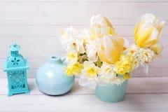 明亮的黄色黄水仙和郁金香花和灯笼在白色 免版税图库摄影