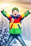 明亮的滑雪夹克衫的英俊的男孩挡雪板在冬天多雪的森林 库存图片