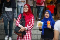 明亮的hijabs的两少女是走和笑在双子楼附近 图库摄影