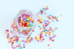 明亮色的糖果店洒在一个玻璃瓶子的星在轻的背景 软的焦点,迷离 免版税库存照片