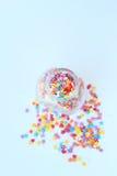 明亮色的糖果店洒在一个玻璃瓶子的星在轻的背景 软的焦点,迷离 免版税图库摄影