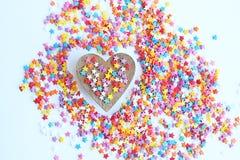 明亮色的糖果店洒星和木心脏在轻的背景,软的焦点,迷离 免版税库存图片