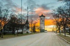 明亮,五颜六色的日落在有塔的小镇和教会 免版税库存图片