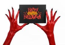 明信片和愉快的万圣夜题材:有拿着与词在白色的愉快的万圣夜的黑钉子的红魔手一个纸牌 库存图片