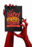 明信片和愉快的万圣夜题材:有拿着与词在白色的愉快的万圣夜的黑钉子的红魔手一个纸牌 免版税库存图片
