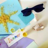 明信片夏天,从橙色海盐,太阳镜,在轻的背景,顶视图的蓝色色纸的阳光 库存图片