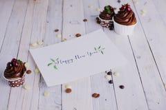 明信片用在白色木背景的祝贺和巧克力杯形蛋糕莓果 字法 艺术 免版税库存图片