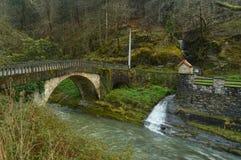 明信片美丽的照片与一条勇敢的河、一座罗马桥梁和一艘美妙的微型居住船的在Gorbeia自然公园  形成弧光的 图库摄影