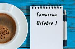 明天在工作笔记薄-写的10月在早晨咖啡杯附近在不拘形式的蓝色桌工作场所 底9月 免版税图库摄影