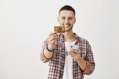 明智地花费您的金钱 拿着智能手机的愉快的可爱的男学生,当拉扯往照相机和显示时的手 免版税库存照片
