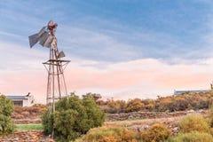 黄昏与一台残破的风车的农厂场面 库存图片