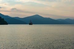 黄昏薄雾的Mountain湖与古板的船 图库摄影