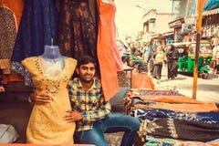 年轻贸易商与女性时尚一起使用在繁忙的农贸市场纺织品商店  免版税图库摄影