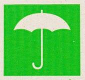 易碎的标志的伞图象在纸板的。 免版税库存照片