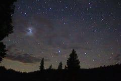 星、树和山夜间照片  免版税库存照片
